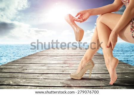 gray wooden pier on ocean and woman legs and heels