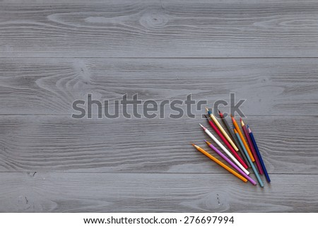 Gray, wooden table top view of the artist. On the table lay the colored pencils to draw. - stock photo