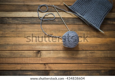 Gray wool yarn ball. Woolen thread with incomplete knitting winter hat on wooden table.  - stock photo