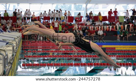 GRAZ, AUSTRIA - APRIL 05, 2014:  Swimmers start at the women'S 50m freestyle event in an indoor swimming meeting. - stock photo