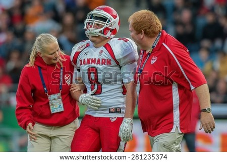GRAZ, AUSTRIA - MAY 31, 2014: LB Mikkel Vangsgard (#8 Denmark) is led off the field after an injury in match against Austria during the EFAF European Championships 2014 in Austria.. - stock photo