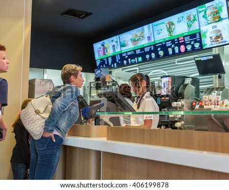 GRAZ, AUSTRIA - SEPTEMBER 12, 2015: people make an order in McDonald restaurant. McDonald is the world's largest chain of hamburger fast food restaurants founded in the United States. - stock photo