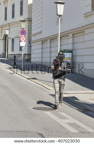 GRAZ, AUSTRIA - SEPTEMBER 12, 2015: Unrecognized cameraman getting video on Freiheitsplatz. Graz is the capital of federal state of Styria and second largest city in Austria. - stock photo