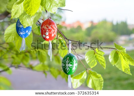 Grean Easter background with painted wooden eggs hanging from tree branches. This image is blurred, shallow DOF, focus on red egg. - stock photo