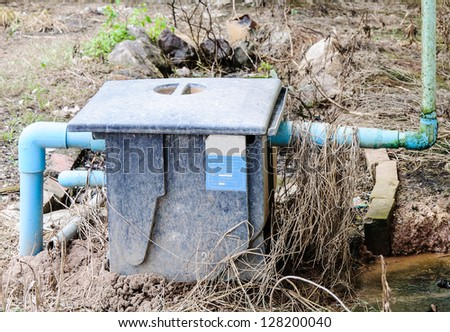Grease traps box on the ground behind canteen. - stock photo