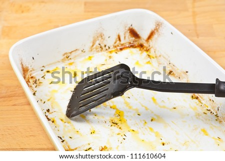 Greased ceramic tray with remains of olive oil after roasting food in the oven - stock photo