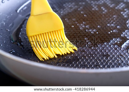 Greasing dripping pan by yellow silicone brush with olive oil - stock photo