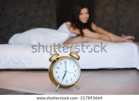 Great alarm clock in the foreground. Close up image of alarm clock over the blurred sleeping woman.sleepy woman waking up and yawning with a stretch while sitting in bed  - stock photo