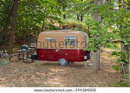 great amazing inviting view of classic retro vintage camp trailer standing in woods on summer beautiful sunny day