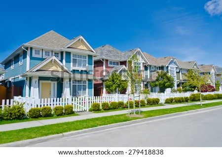 Great and comfortable neighborhood. A row of townhouses behind wooden fence at the empty street. - stock photo