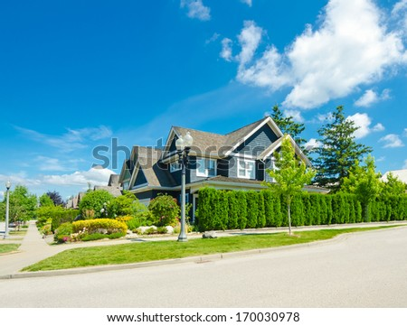 Great and comfortable neighborhood and a luxury house behind the nicely trimmed green fence and sidewalk at the empty street in the suburbs of Vancouver, Canada. Keeps privacy and security.
