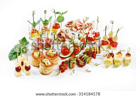 great attractive set of canapes with vegetables, cheese, fruits, berries, salami, seafood, meat and decoration on white background studio isolated - stock photo