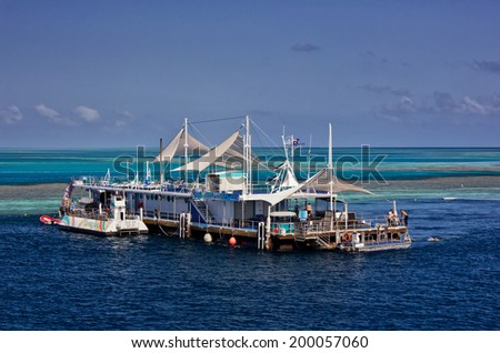 GREAT BARRIER REEF, AUSTRALIA - October 14,2013: Staff perform end-of-day tasks on the Reefworld pontoon. Visitors can snorkel, dive, ride a semi-submersible or stay overnight under the stars. - stock photo