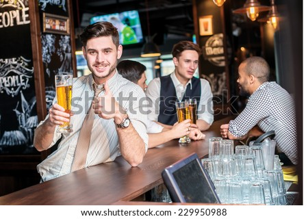 Great beer. Three cheerful friends met at the bar and drink a beer while the bartender is standing on the bar. Friends having fun together - stock photo