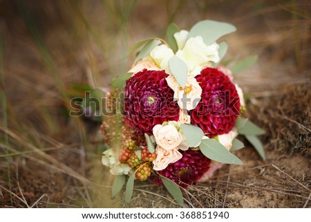 Great bridal bouquet of roses, peonies, dahlias, asters and dried flowers lying on the ground in the forest - stock photo