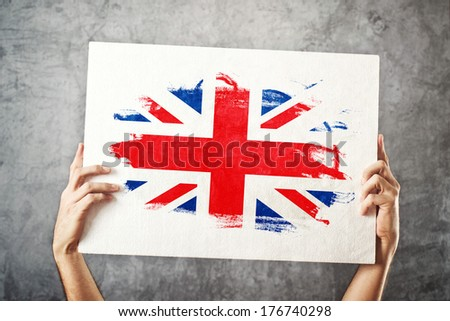 Great Britain flag. Man holding banner with British Flag. Supporting national team, patriotism concept. - stock photo