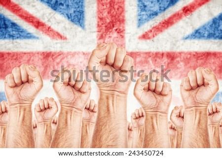 Great Britain Labor movement, workers union strike concept with male fists raised in the air fighting for their rights, British national flag in out of focus background. - stock photo