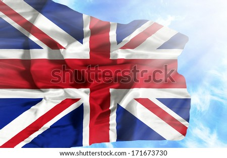 Great Britain waving flag against blue sky with sunrays - stock photo