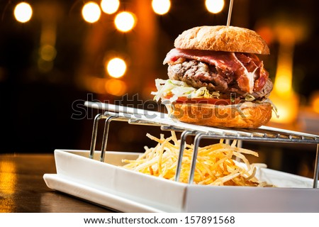 Great burger with beef meat, ham and fried potatoes. - stock photo