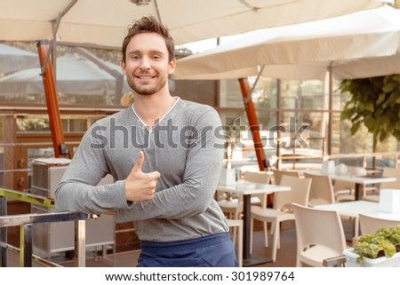 Great  cafe. Portrait of handsome smiling muscular cafeteria worker standing with thumbs up. - stock photo