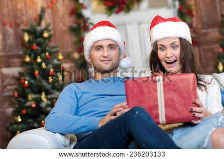 Great Christmas surprise. Couple in love is sitting in festive Christmas decorated living room. Girl is really excited about getting her New Year present