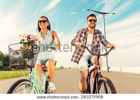 Great day for cycling. Low angle view of cheerful young couple smiling and riding on bicycles  - stock photo