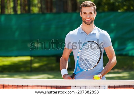 Great day to play! Cheerful young man in polo shirt holding tennis racket and ball while standing on tennis court  - stock photo