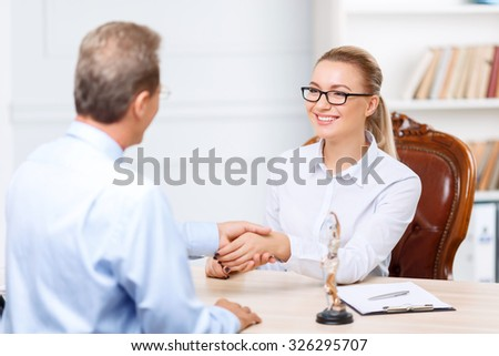 Great deal. Pleasant upbeat professional lawyer sitting at the table and shaking hands while having conversation