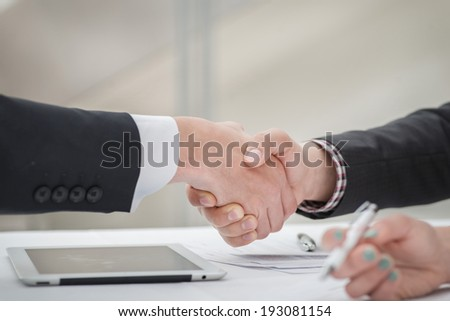 Great deal! Young businessmen shaking hands with each other in the business center. Successful businessmen on a corporate meeting close-up view