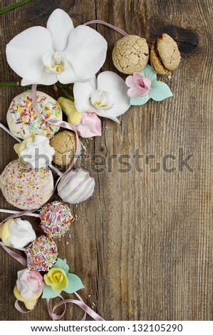 Great diversity of sweets on wooden background. Blank space on wooden board. White orchid flowers, cake pops, muffins, macaroons and marshmallows together. - stock photo