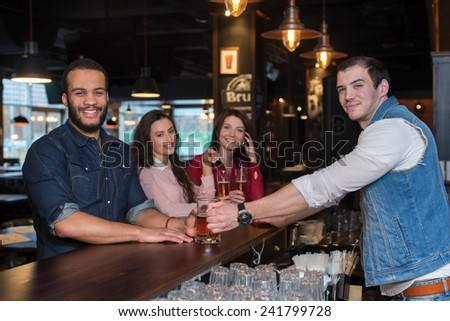 Great evening with beer. Portrait of young and handsome afro american guy. He is standing at the bar counter and talking with barman, while drinking beer. His friends are standing with beer behind