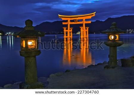 Great floating gate (O-Torii) on Miyajima island near Itsukushima shinto shrine, Japan shortly after the sunset with lit lanterns on the shore - stock photo