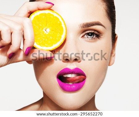 Great food for a healthy lifestyle. Beautiful young shirtless woman with pink lips and manicure holding piece of orange in front of her eye while standing against white background - stock photo