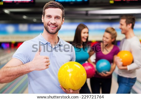 Great game! Handsome young men holding a bowling ball  and thumb up while three people communicating against bowling alleys