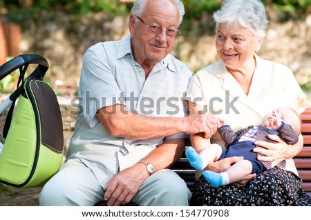 Great grandfather and grandmother and little baby boy on a bench in the park  - stock photo
