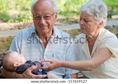 Great grandfather and grandmother and little baby boy on a bench in the park