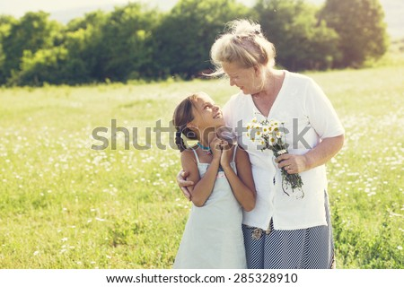 Great-grandmother and granddaughter standing in flower field in sunlight - stock photo