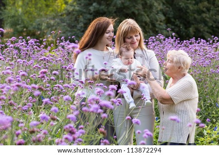 Great-grandmother, grandmother, mother holding a baby in a beautiful lavender field - stock photo