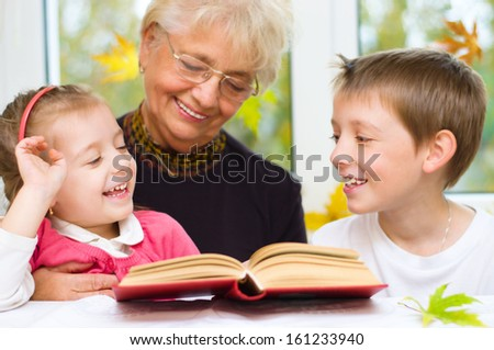 Great-grandmother reading a book for grandchildren at home - stock photo