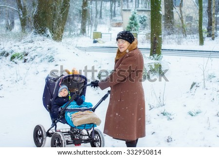 Great-grandmother walking with baby boy in pram during snowfall in winter. Happy family. Carefree childhood and generation. - stock photo