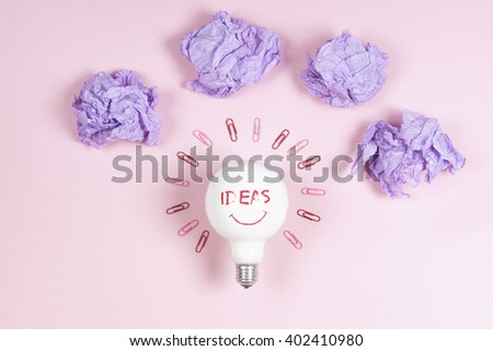 great idea concept with crumpled colorful paper and light bulb on light background. Creative brainstorm concept business idea.  female hand holding light bulb. - stock photo