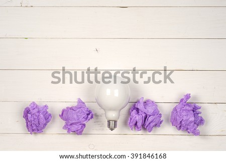 great idea concept with crumpled colorful paper and light bulb on wooden background - stock photo
