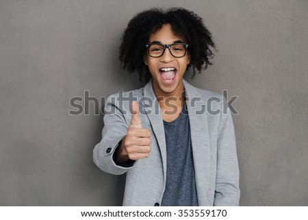 Great job! Cheerful young African man showing his thumb up and making a face while standing against grey background - stock photo