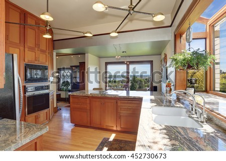 Great kitchen room with granite counter tops, built-in appliances, pendant lights and light tones cabinets.