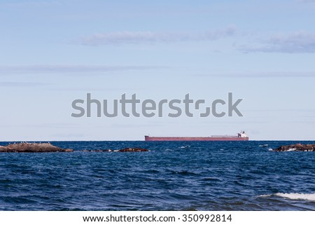 Great Lakes Ore Boat - freighter passing behind rocky outcroppings on Lake Superior.  Horizon is at the one-third line to allow for copy in the sky. - stock photo