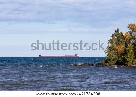 Great Lakes Shipping - Great Lakes oar boat on the horizon passing behind a rocky island with trees.  Low hanging clouds and plenty of room for copy if needed. - stock photo