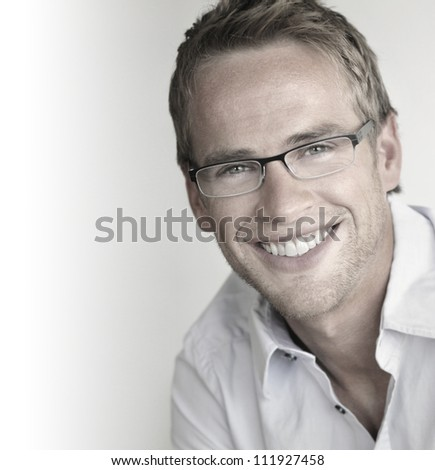 Great looking young man with perfect smile in trendy glasses - stock photo