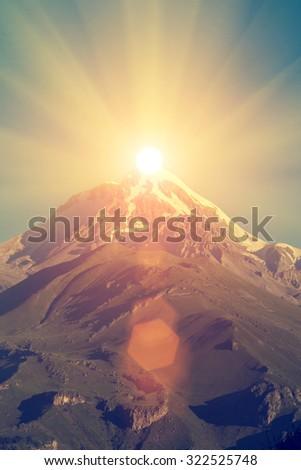 Great mountain peak with sun - stock photo