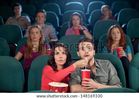 Great movie! Young couple feeding each other while watching movie at the cinema - stock photo