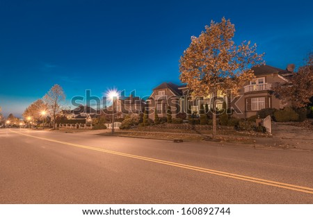 Great neighborhood. A row of the luxury houses at the empty street at dusk, night time in suburbs of Vancouver, Canada. - stock photo
